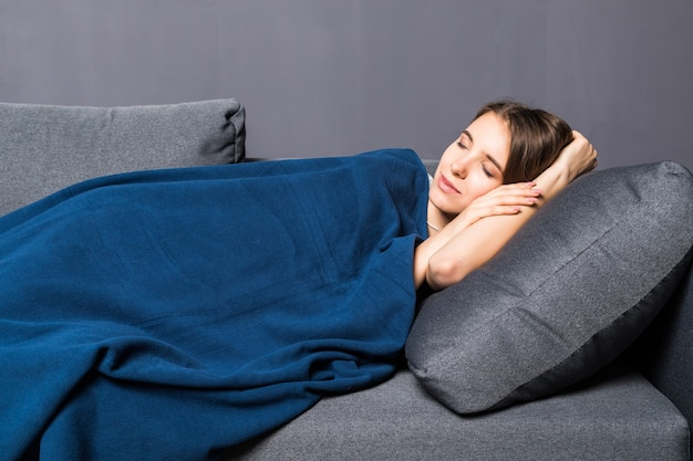 Jeune fille endormie sur un canapé recouvert de couvre-lit bleu sur fond gris