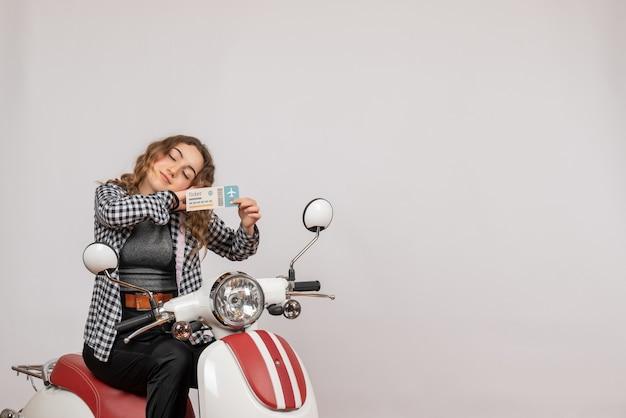 Jeune fille endormie sur un cyclomoteur tenant un billet de voyage sur gris