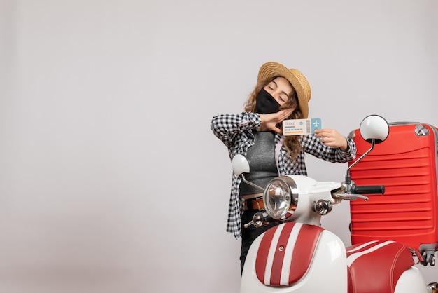 Jeune fille endormie avec un masque noir tenant un ticket debout près d'un cyclomoteur rouge