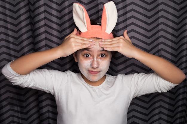 Jeune fille enduit le visage d'argile cosmétique ou de boue.