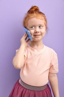Jeune fille enfant communique sur le téléphone mobile sourit et parle isolé sur violet