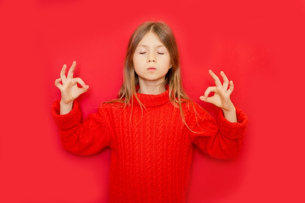 Jeune fille enfant debout sur fond isolé rouge détendu et souriant les yeux fermés faisant le geste de méditation avec les doigts concept de yoga
