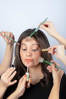 Jeune fille entourée de mains de maquilleurs avec pinceaux, rouge à lèvres et mascara près de son visage.