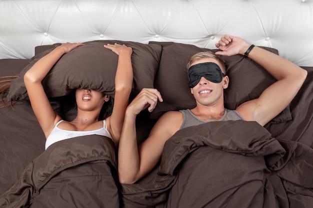 La jeune fille essaie de s'endormir en se couvrant la tête avec un oreiller