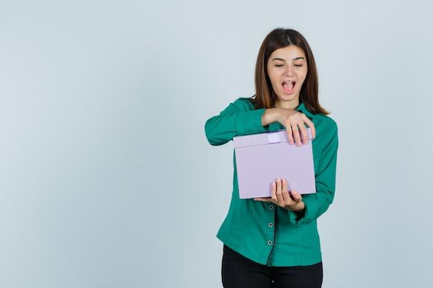 Jeune fille essayant d'ouvrir la boîte-cadeau en chemisier vert, pantalon noir et à la recherche excitée. vue de face.