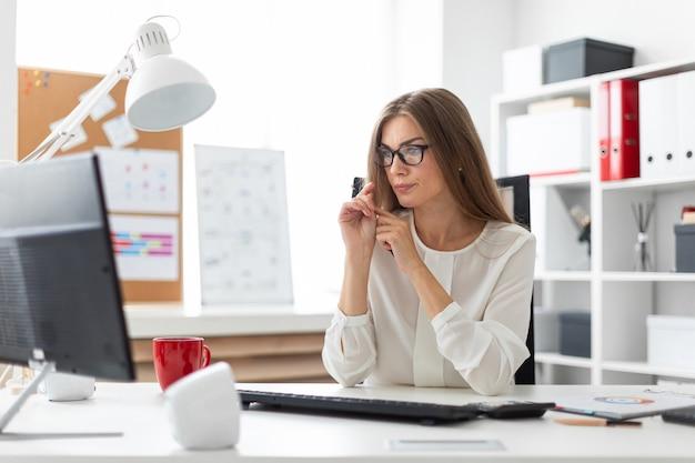 Une jeune fille est assise au bureau du bureau, tenant un crayon à la main et regardant l'écran.