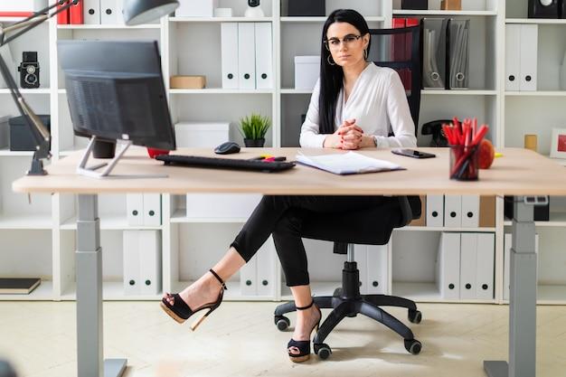 Une jeune fille est assise au bureau d'ordinateur. à côté de la fille se trouvent des documents et un marqueur.