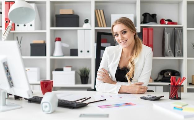 Une jeune fille est assise au bureau de l'ordinateur dans le bureau.