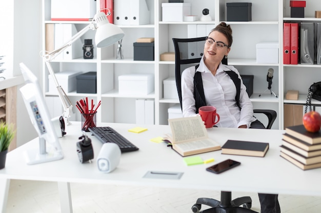 Une jeune fille est assise à un bureau d'ordinateur dans le bureau et tient une tasse rouge dans ses mains.
