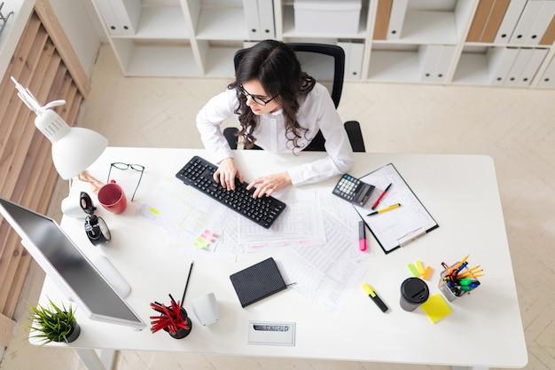 Une jeune fille est assise dans le bureau devant l'ordinateur et travaille avec des documents.