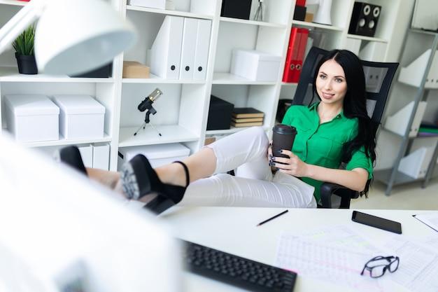 Une jeune fille est assise dans le bureau, a jeté ses jambes sur la table et tient un verre de café.