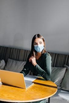 Une jeune fille est assise dans un café, portant un masque et travaillant sur un ordinateur.