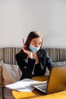 Une jeune fille est assise dans un café portant un masque et travaille devant un ordinateur.