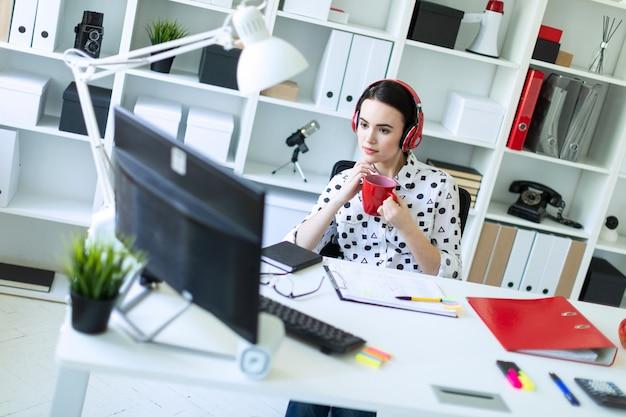 Une jeune fille est assise dans les écouteurs à une table du bureau, elle tient une tasse rouge dans ses mains et regarde l'écran.