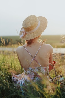 La jeune fille est assise derrière elle en regardant le coucher du soleil