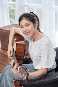 La jeune fille est assise et joue de la guitare sur la chaise.