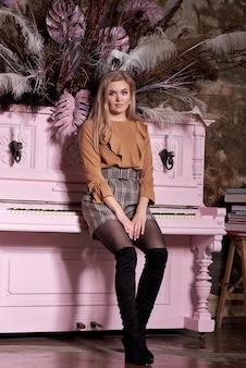Jeune fille est assise sur un piano rose. portrait de beauté d'une blonde en short un vieux mur de briques
