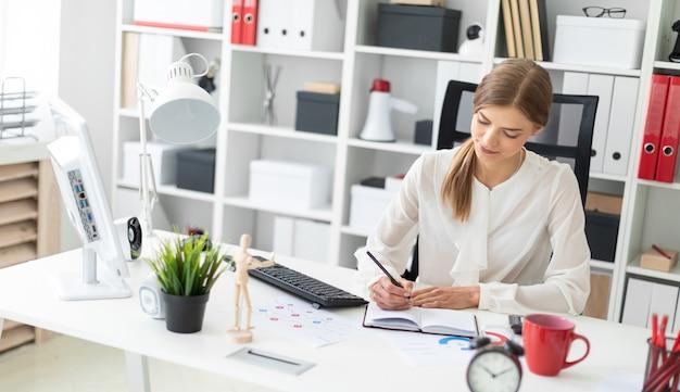 Une jeune fille est assise à une table dans le bureau et écrit avec un crayon dans un cahier.
