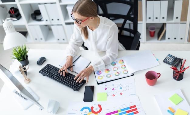 Une jeune fille est assise à une table dans le bureau, tenant un crayon à la main et tapant sur le clavier. avant la fille il y a des diagrammes.