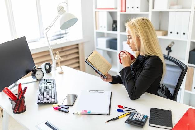 Une jeune fille est assise à une table dans le bureau, tenant une tasse et lisant un livre.