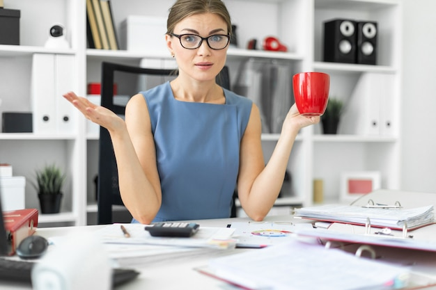 Une jeune fille est assise à une table dans le bureau, tenant une tasse rouge à la main et travaillant avec des documents.