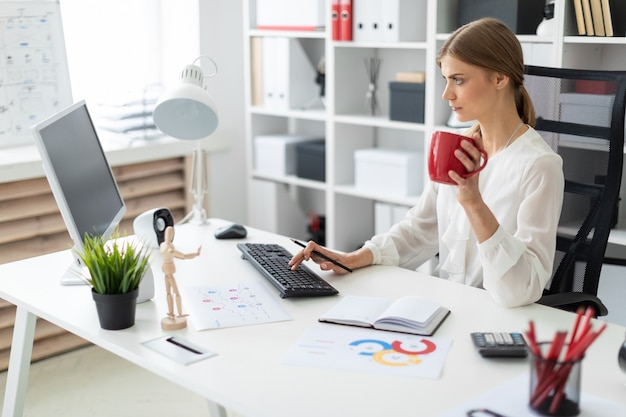 Une jeune fille est assise à une table dans le bureau, tenant une tasse rouge à la main et travaillant à l'ordinateur.
