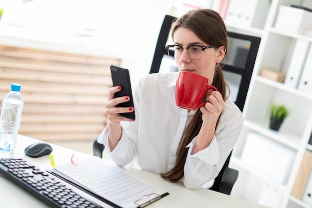 Une jeune fille est assise à une table dans le bureau, tenant un téléphone et une tasse rouge à la main.