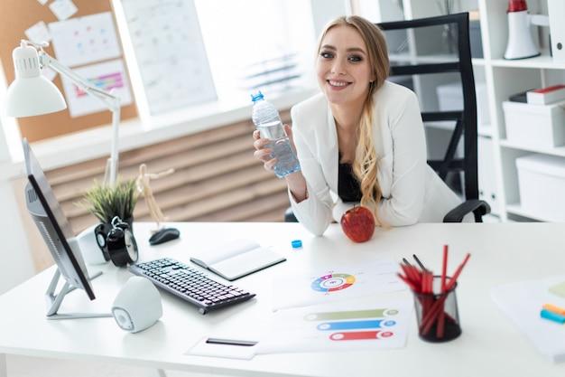 Une jeune fille est assise à une table dans le bureau et tient une bouteille d'eau à la main. avant la fille sur la table est une pomme.