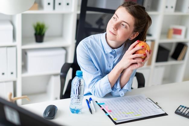 Une jeune fille est assise à une table dans le bureau et tient une pomme dans sa main.