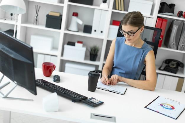 Une jeune fille est assise à une table dans son bureau et écrit un stylo dans son cahier.