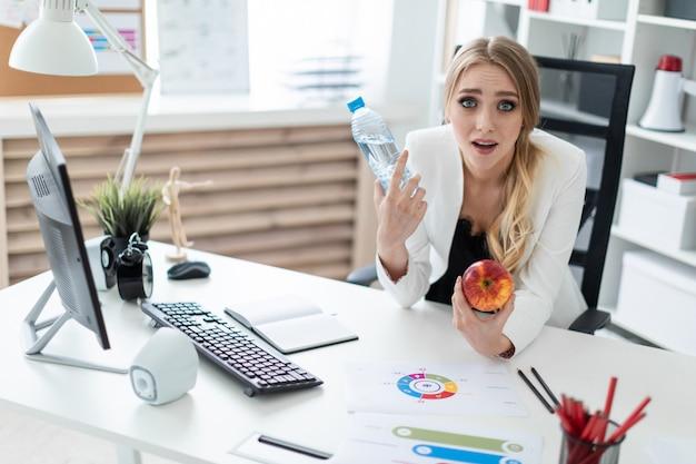 Une jeune fille est assise à une table dans son bureau et tient une bouteille d'eau et une pomme dans ses mains.