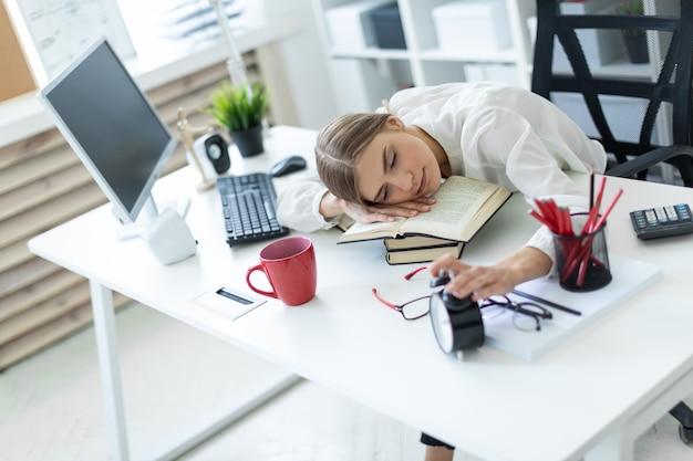Une jeune fille est assise à la table du bureau, pose sa tête sur la table et tient son réveil-matin.