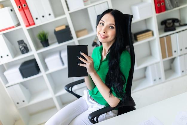 Une jeune fille est assise à la table du bureau et tient un cahier dans ses mains.