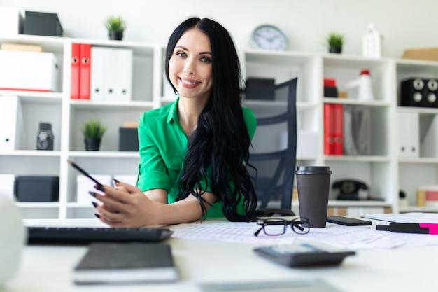 Une jeune fille est assise à la table du bureau et tient un crayon dans ses mains.