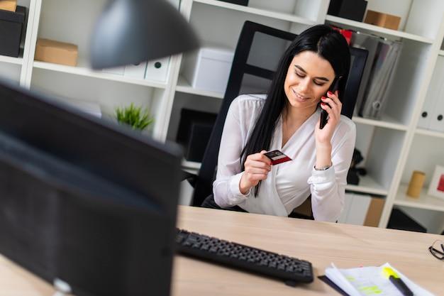 Une jeune fille est assise à une table, tenant une carte bancaire à la main et parle au téléphone.