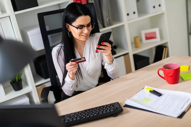Une jeune fille est assise à la table, tenant une carte bancaire et un téléphone.