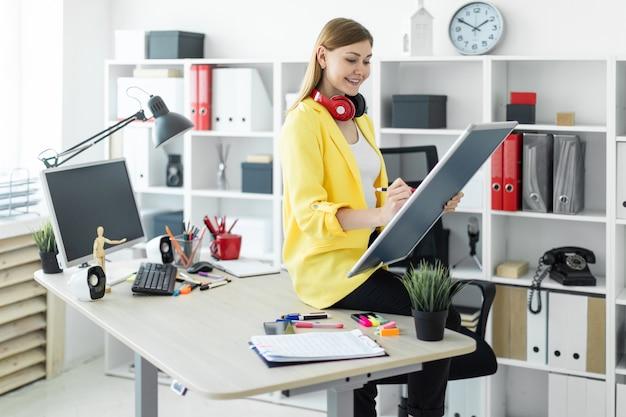 Une jeune fille est assise sur une table et tient un marqueur et un tableau magnétique dans ses mains.