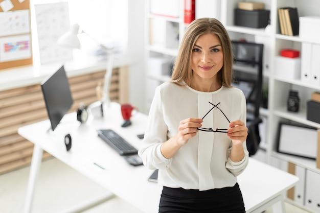 Une jeune fille est debout, appuyée sur une table dans le bureau et tenant des lunettes à la main.