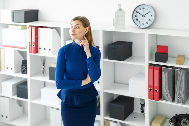 Une jeune fille est debout dans le bureau près de l'étagère.