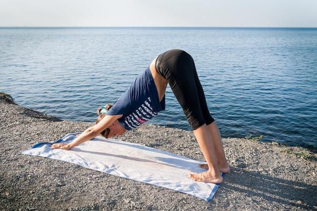 Jeune fille est debout dans un chien de yoga pose sur une côte de mer pierreuse le matin de l'été.