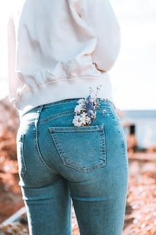 La jeune fille est debout, le dos en jean bleu, des fleurs dans sa poche.