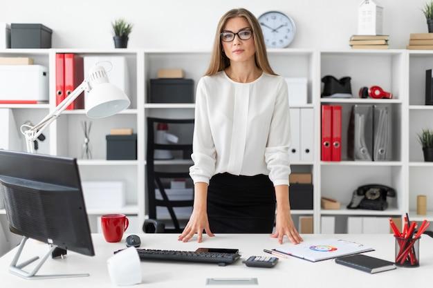 Une jeune fille est debout près d'une table dans le bureau.