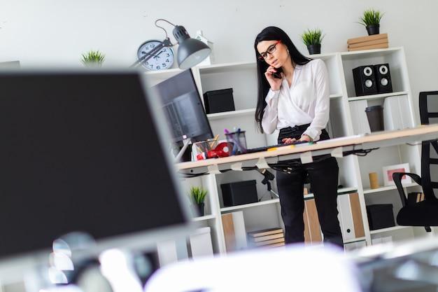 Une jeune fille est debout près de la table, parle au téléphone et tape sur le clavier. avant la fille est un tableau magnétique et des marqueurs.