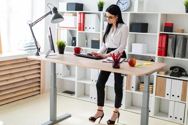 Une jeune fille est debout près de la table et tape du texte sur le clavier. à côté de la jeune fille, des documents et un marqueur.