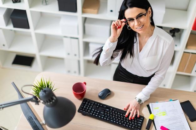 Une jeune fille est debout près de la table et tape du texte sur le clavier