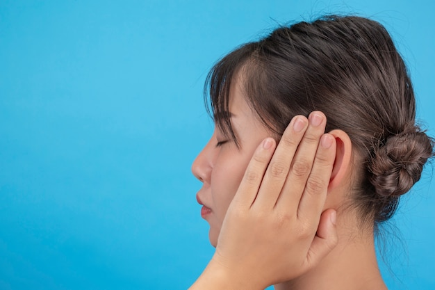 La jeune fille est malheureuse et essaie de fermer les oreilles avec ses mains sur le mur bleu.