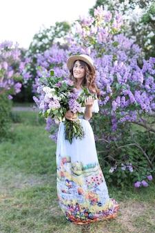 Jeune fille est titulaire d'un bouquet de fleurs lilas fille au chapeau de paille debout dans le jardin d'été