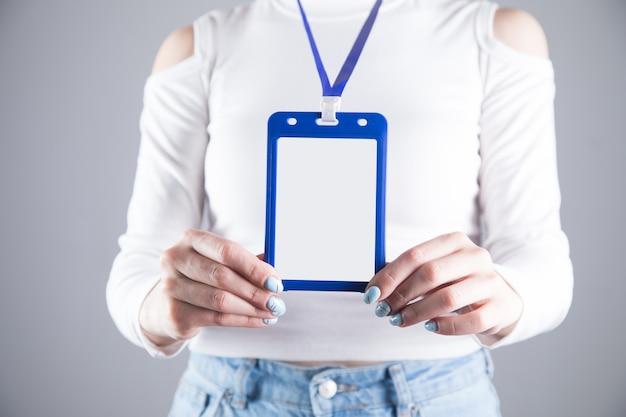 Jeune fille est titulaire d'une carte d'identité sur une scène grise