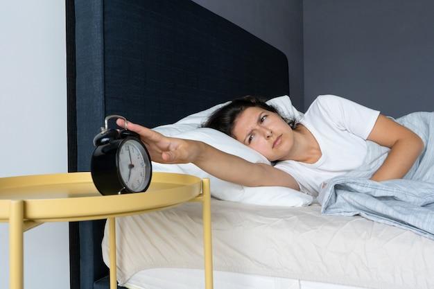 La jeune fille éteint le réveil ennuyeux pour continuer à dormir. dormez un peu plus. c'est une matinée difficile. l'heure de se lever.