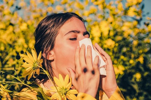 Jeune fille éternue et tenant un mouchoir en papier dans une main et un bouquet de fleurs dans l'autre. jeune femme